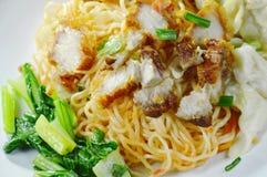 Séchez les nouilles chinoises d'oeufs complétant le porc et la boulette croustillants du plat photographie stock libre de droits