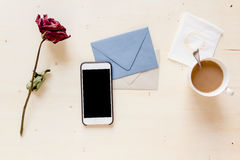 Séchez rose avec le téléphone sur la lettre et le café de papier Photographie stock