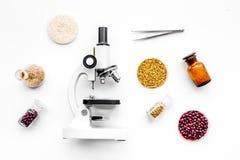 Sécurité alimentaire Blé, riz et haricots rouges près de microscope sur la vue supérieure de fond blanc photographie stock