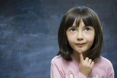Séjour adorable d'écolière près de tableau noir d'école. Image stock