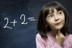 Séjour d'écolière près de tableau noir d'école. Photos libres de droits
