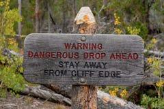 Séjour dangereux de baisse de panneau d'avertissement en avant à partir du bord de falaise photographie stock libre de droits