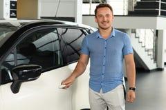 Séjour de client près de voiture au concessionnaire automobile images stock