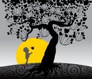 Séjour de petit garçon sous le grand arbre Image stock