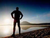 Séjour de silhouette de sportif dans le coucher du soleil orange lumineux sur la plage Rester d'homme Photographie stock