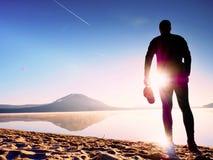 Séjour de silhouette de sportif dans le coucher du soleil orange lumineux sur la plage Rester d'homme Photographie stock libre de droits