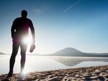 Séjour de silhouette de sportif dans le coucher du soleil orange lumineux sur la plage Rester d'homme Images libres de droits
