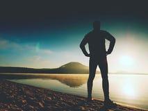 Séjour de silhouette de sportif dans le coucher du soleil orange lumineux sur la plage Rester d'homme Photos stock