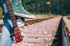 Séjour de voyageur d'homme sur le chemin de fer - espadrilles et plan rapproché i de guitare Photos libres de droits