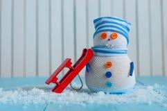 Séjour fait main de bonhomme de neige avec le traîneau rouge sur la lumière Photo stock