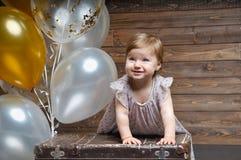 Séjour mignon assez petit de fille près d'une grande vieille valise de vintage Photo libre de droits