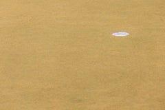 Sélectif concentré sur le trou de golf sur l'herbe jaune sèche du cou de golf Photographie stock libre de droits