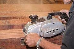 Sélectif sur la planeuse électrique est travaillé avec le charpentier supérieur dans l'atelier de menuiserie Profondeur de zone Image stock