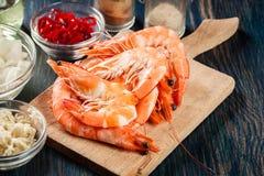 Sélection de crevette prête pour faire frire à l'oignon, à l'ail, au piment et à la chaux sur la planche à découper Photos libres de droits