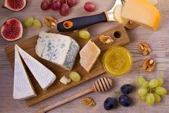 Sélection de fromage sur le fond rustique en bois Plateau de fromage avec différents fromages, servis avec des raisins, des figue Photographie stock