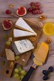 Sélection de fromage sur le fond rustique en bois Plateau de fromage avec différents fromages, servis avec des raisins, des figue Photos libres de droits