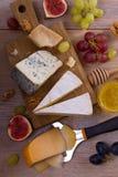 Sélection de fromage sur le fond rustique en bois Plateau de fromage avec différents fromages, servis avec des raisins, des figue Photographie stock libre de droits