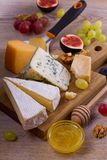 Sélection de fromage sur le fond rustique en bois Plateau de fromage avec différents fromages, servis avec des raisins, des figue Images libres de droits