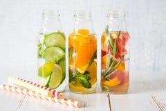Sélection de l'eau infusée dans des bouteilles en verre, fond en bois rustique Images stock