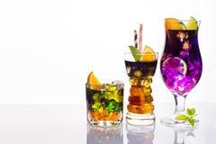 Sélection des boissons de fête colorées, des boissons alcoolisées et des cocktails en verres élégants sur le blanc Photo stock