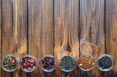 Sélection des thés assortis dans de petites cuvettes transparentes sur le fond naturel photographie stock