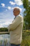 Sénior aposentado por uma beira do lago imagem de stock royalty free