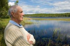 Sénior aposentado por uma beira do lago imagem de stock