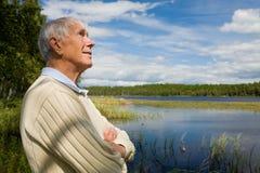 Sénior aposentado por uma beira do lago fotografia de stock