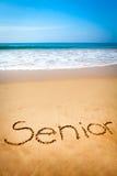 Sénior da palavra escrito na areia, na praia tropical fotos de stock