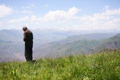 Sénior Praying nas montanhas imagens de stock royalty free