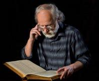 Sénior que lê o livro Fotografia de Stock Royalty Free