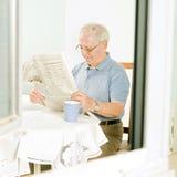 Sénior que lê um jornal fotos de stock
