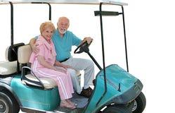Séniores do carro de golfe isolados Imagens de Stock Royalty Free
