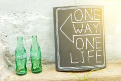 SÉOUL, CORÉE - 9 AOÛT 2015 : Deux bouteilles vides de Coca-Cola à côté de plat en céramique avec des mots Image stock