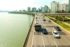SÉOUL, CORÉE - 14 AOÛT 2015 : Voitures passant la route de route le long du fleuve Han avec des affaires et la zone résidentielle Photographie stock libre de droits