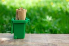 Séparation du papier dans le conteneur vert pour économiser les ressources naturelles image stock