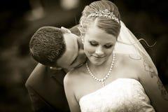 Sépia embrassant la jeune mariée de tatouage sur leur mariage de peau de cou Photos stock