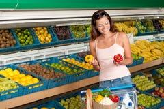 Série da compra - mulher que prende duas pimentas Fotografia de Stock Royalty Free