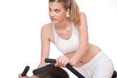 Série de forme physique - jeune femme avec le vélo d'exercice Images libres de droits