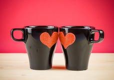 Série de Saint Valentin, tasses de lait avec le coeur décoratif sur la table en bois et fond rouge Photographie stock libre de droits