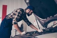 Sérieux, mécanicien de concentré dans l'usage bleu de travail, shir à carreaux image stock