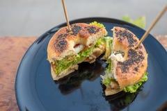 Sésame de noir de Begel avec de la salade de poulet coupée dans la moitié avec le bâton sur le dessus photo stock