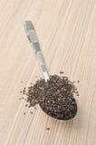 Sésame noir dans la cuillère sur la table en bois Photos stock