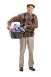 Sênior alegre que mantém uma cesta de lavanderia completa da roupa fotografia de stock royalty free