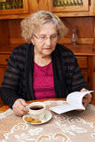 Sênior com leitura do chá Fotografia de Stock