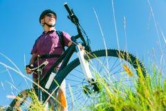 Sênior com o Mountain bike que está no auge de um monte fotografia de stock