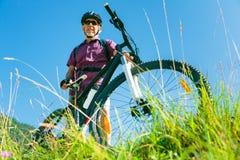 Sênior com o Mountain bike que está no auge de um monte imagem de stock royalty free