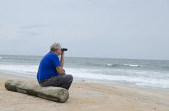 Sênior com os binóculos na praia Imagens de Stock Royalty Free
