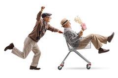 Sênior com os vidros 3D que empurram um carrinho de compras com um outro seni foto de stock royalty free