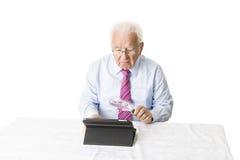 Sênior com tabuleta e lupa Imagens de Stock
